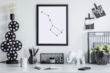 Stylish black and white home decor mock up. Creative desk with blank picture frame or poster, desk objects, office supplies, elephant figure and plants in design pots on a white background.