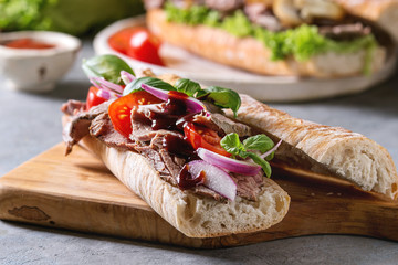 Beef baguette sandwich with tomatoes, basil, red onion served on ceramic plate with ingredients above over grey blue table.