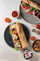 Variety of beef baguette sandwiches with champignon mushrooms, green salad, fried onion, tomatoes served on ceramic plate with ingredients above over white marble background. Flat lay, space