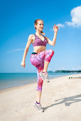 Fitness young woman working out core and glutes with bodyweight workout doing squat exercises on beach.