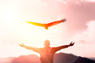 Poster Eagle Man raise hand up on top of mountain and sunset sky with eagle bird fly abstract background.