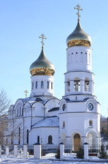 Orthodox church. White with two towers and Golden domes against the blue sky. Winter.