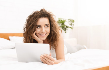 Cheerful young woman lying in bed with tablet