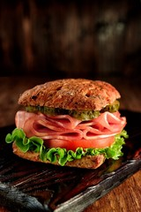 Keuken foto achterwand Bakkerij resh sandwich with ham, cheese, bacon, tomatoes, salad, cucumbers and onions on a wooden cutting Board