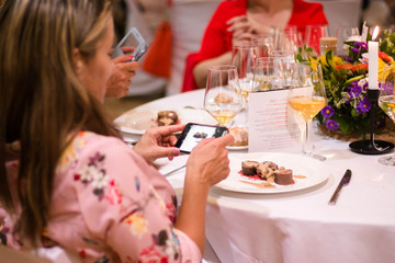 Woman taking a picture with her smartphone of her food in a fine table restaurant