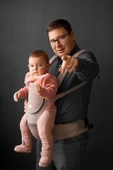 Fathre and his kid in baby carrier at the grey background wall, baby wearing concept
