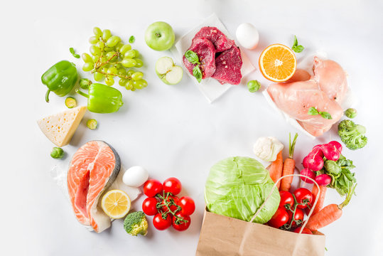 Healthy food shopping concept, Balanced diet ingredient - meat, fish, fruit, vegetables. Fresh foods with paper shopping bag, top view on white background copy space