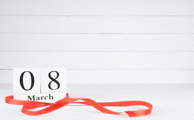 Womens day concept, happy womens day, international women's day. March 8 text wooden block calendar with red ribbon on white wooden background.