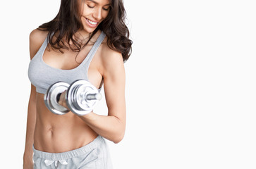 Cheerful sportswoman doing bicep curl with dumbbell