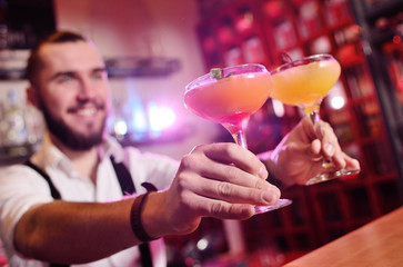 handsome bartender prepares an orange alcoholic cocktail and smiles on the background of a bar or a night club