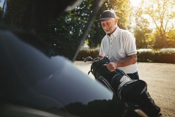 Senior man packing his golf clubs in a car trunk