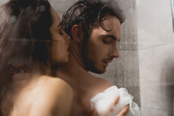 handsome man and attractive woman hugging and taking shower with loofah