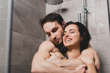 naked man and attractive woman hugging and smiling in shower cabin