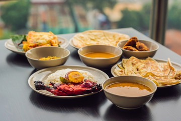 Assorted indian food on dark wooden background. Dishes and appetizers of indian cuisine. Curry, butter chicken, rice, lentils, paneer, samosa, naan, chutney, spices. Bowls and plates with indian food