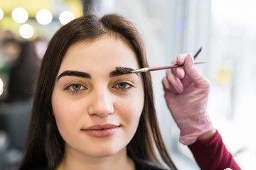 Make-up artist combing eyebrow on model face.