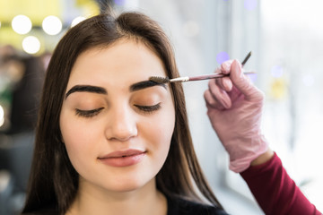 Make-Up. Beautician Hands Doing Eyebrow Tattoo On Woman Face.Permanent Brow Makeup In Beauty Salon. Closeup Of Specialist Doing Eyebrow For Female.