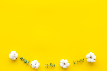 Flowers composition on yellow desk with fresh eucalyptus branches and cotton. Flat lay, top view, copy space