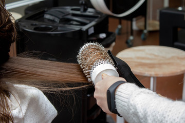 a hairdresser master doing blow-drying in a beauty salon