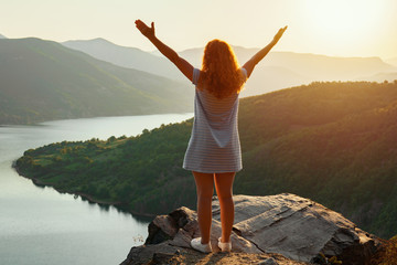 A relaxed red-haired woman in a dress is standing on top of a high mountain against the backdrop of a large mountain lake and spinning with happiness, raising her hands up. Bright sunset on the lake