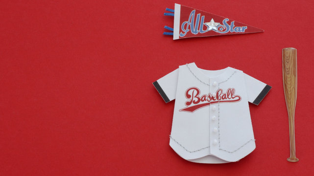 Baseball jersey, All star banner and bat laying flat on a red background with writing space