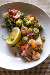 quinoa salad with tomato, cucumber, lemon and avocado on a white plate