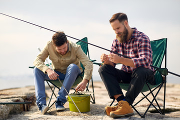 leisure and people concept - friends or fishermen adjusting fishing rods with bait on pier