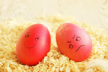 Two Easter eggs with the drawn persons. Joyful and the sad broken egg. Traditional game with breaking eggs