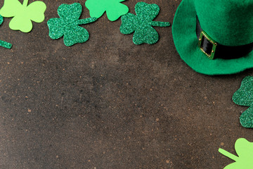 St.Patrick 's Day. a holiday. Frame of green leaves of clover and leprechaun hat on a brown background. top view. space for text