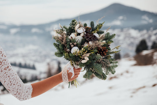 Winter wedding bouquet. Bride   holds a wedding winter bouquet. Winter  wedding style.