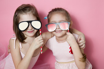 Two little friends in pink clothes having fun building faces and putting glasses to his face. On a pink background-image
