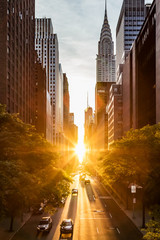 Sunset light shining on the buildings and cars on 42nd Street in Midtown New York City around the...