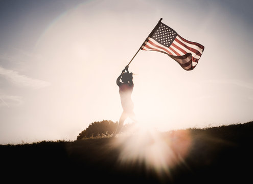 Silhouette of woman holding American flag while running outdoors