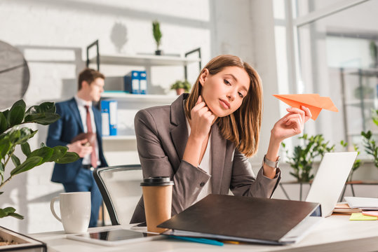 tired businesswoman holding paper plane near laptop with coworker on background, procrastination concept