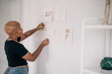 Calligraphy artist sticking drawings on wall