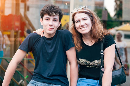 Happy mother hug her teenage son and rejoices because she is reconciled with her son with whom she had a complicated relationship