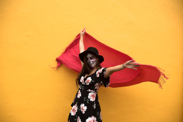 Woman with painted face standing against yellow background