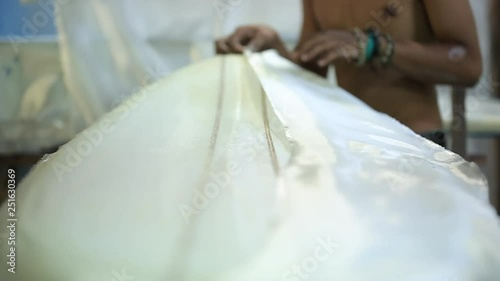 Worker apply fiberglass and epoxy resin coating after modelling a