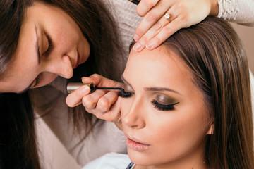 Make up artist applying eyeliner on female client's eyelids