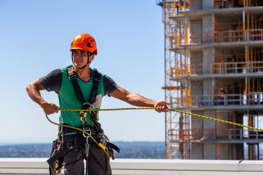High rise rope technician window cleaner is working on a construction site during a sunny summer day. Taken in Burnaby, Vancouver, BC, Canada.