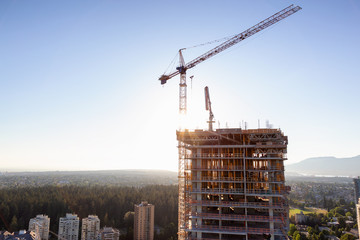 Aerial view of a residential building construction site during a vibrant summer sunset. Taken in Burnaby, Vancouver, BC, Canada.