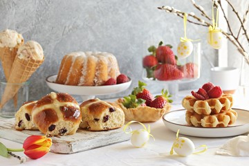 Easter festive dessert table with hot cross buns, cakes and waffles.