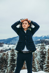A wonderful man dressed in a suit holds his wavy hair against the background of the winter mountains