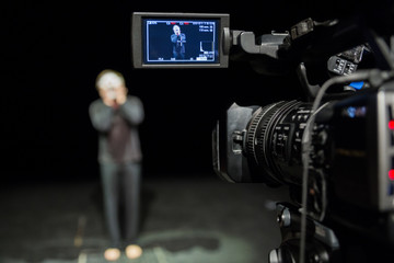 Actor in front of the camera. LCD display on the camcorder. Filming in the interior.