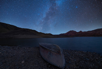 Beautiful night landscape, small boat, starry night over the lake and mountain.