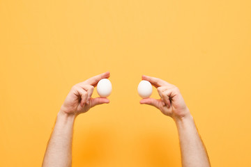 Men's hands hold two white eggs on a yellow background. Hands with eggs are isolated on a yellow background. Background. Copyspace