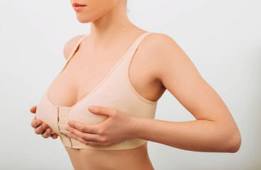 Woman wearing at special slimming bra, after breast augmentation