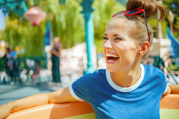 happy trendy woman in amusement park enjoying attraction