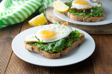 Sandwich or bread toast with avocado and a fried egg on a white plate on rustic wood table. Healthy food. Healthy eating.