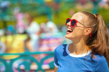 smiling traveller woman in amusement park having fun time