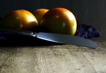 tomato and knife on cutting board